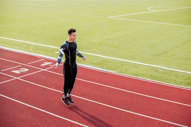 Male athlete skipping on red race track in the stadium