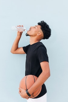 Male athlete standing with basketball and drink water on soft blue background