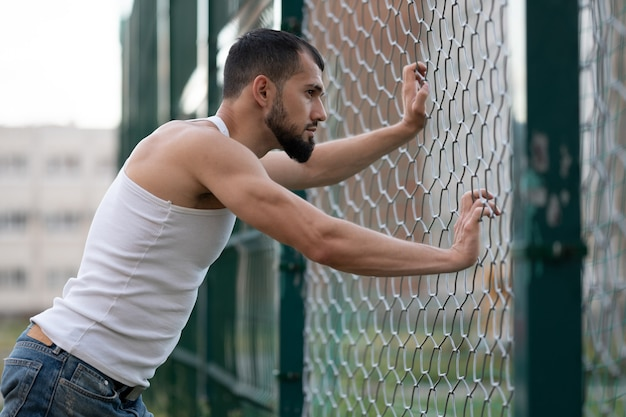 A male athlete stands on the playground and looks through a gap in the fence. a man looks into the distance in the city