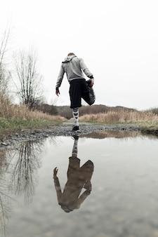 彼の足を水たまりの近くに伸ばしている男性アスリート