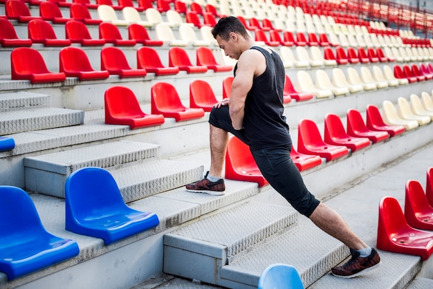 Male athlete stretching his leg on staircase near bleachers