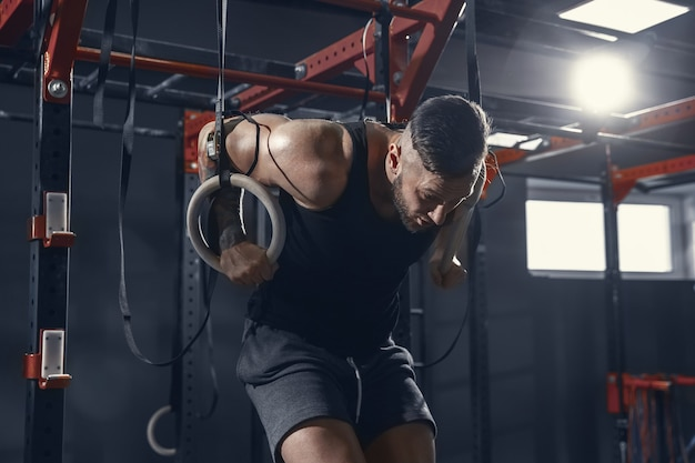 The male athlete training hard in the gym