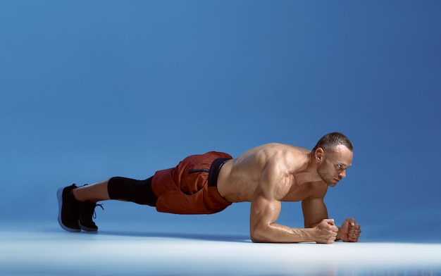 Male athlete trains his abs standing on his elbows, workout in studio, blue background. one man with athletic build, shirtless sportsman in sportswear, active healthy lifestyle