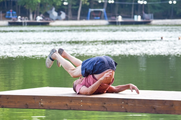 Male athlete trains on the pier outside in the summer park. morning gymnastic sports training.