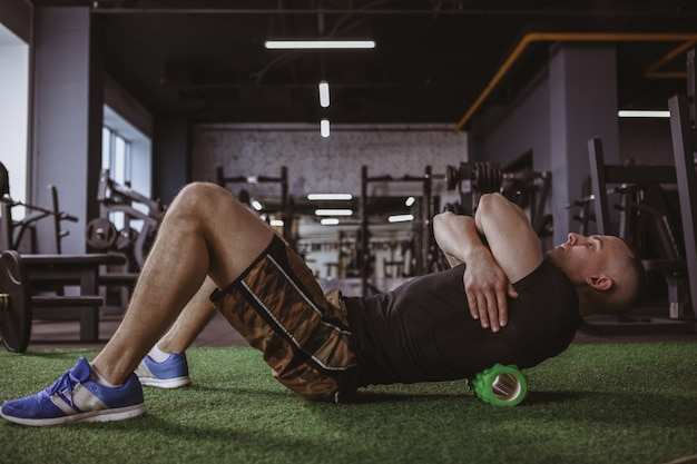Male athlete using foam roller at the gym