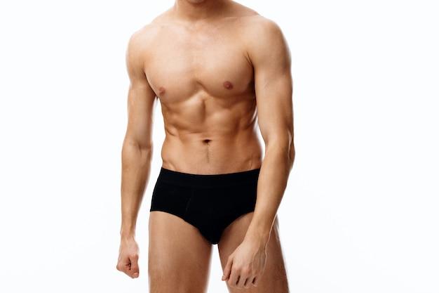 胃の裸の胴体に上腕二頭筋と立方体を持つ男性アスリート