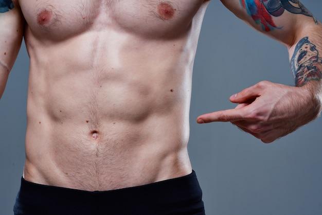 彼の胃の裸の胴体の入れ墨のボディービルダーのフィットネスに立方体を持つ男性アスリート