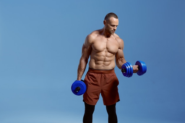 Male athlete with dumbbells poses in studio