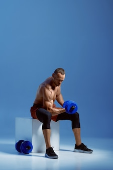 Male athlete with dumbbells sitting on cube in studio, blue background. one man with athletic build, shirtless sportsman in sportswear, active healthy lifestyle