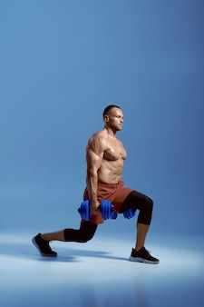 Male athlete with dumbbells, training in studio