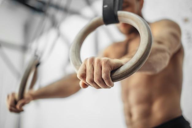ジムで体操リングを持つ男性の運動選手。