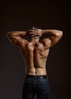 Male athlete with muscular body, back view