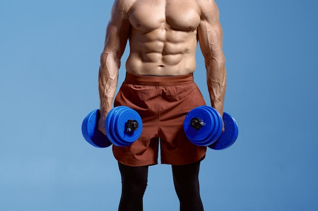 筋肉質の体を持つ男性アスリートは、スタジオ、青い背景でダンベルを保持しています。アスリートビルド、スポーツウェアの上半身裸のスポーツマン、アクティブな健康的なライフスタイルを持つ一人の男