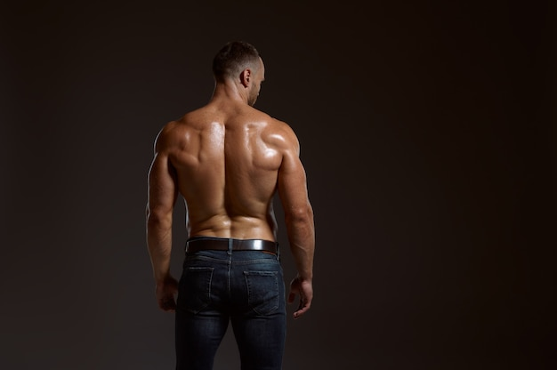 Male athlete with muscular body poses in studio