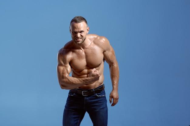 筋肉質の体を持つ男性アスリートは、スタジオ、青い背景で彼の上腕二頭筋を示しています。アスリートビルド、ジーンズパンツの上半身裸のスポーツマン、アクティブな健康的なライフスタイルを持つ一人の男