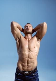 筋肉質の体を持つ男性アスリートは、スタジオ、青い背景で彼の力を示しています。アスリートビルド、ジーンズパンツの上半身裸のスポーツマン、アクティブな健康的なライフスタイルを持つ一人の男