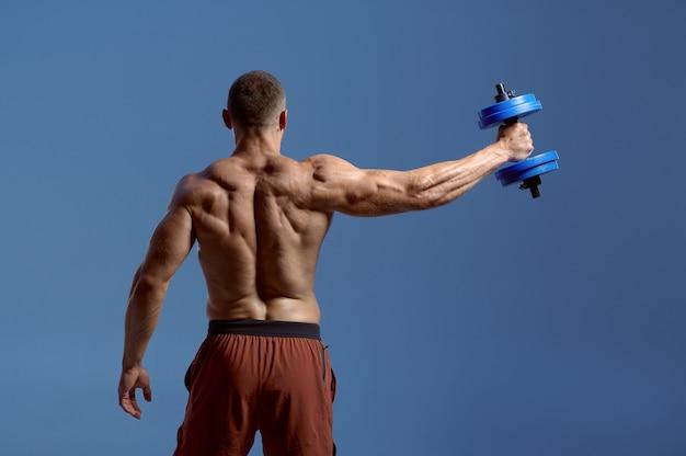 男性アスリートは、ダンベル、スタジオでのトレーニング、青い背景で動作します。アスリートビルド、スポーツウェアの上半身裸のスポーツマン、アクティブな健康的なライフスタイルを持つ一人の男