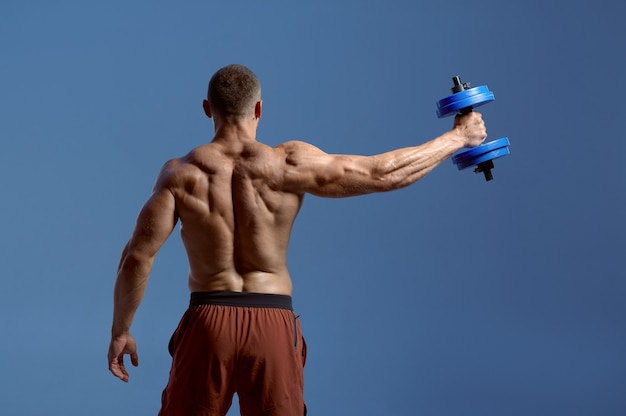 Male athlete works with dumbbells, workout in studio, blue background. one man with athletic build, shirtless sportsman in sportswear, active healthy lifestyle