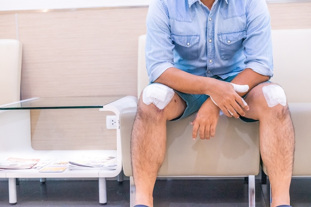 Male athlete wraps knee injury with bandage. human health care and medicine concept
