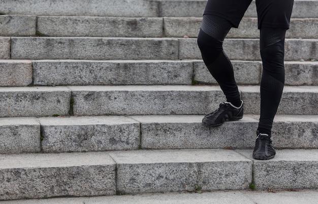 Gambe atletiche maschii che camminano sulle scale