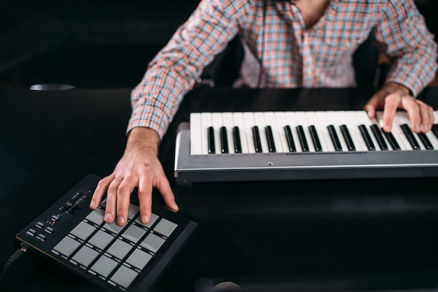 Male audio engineer hands on musical keyboard, closeup. digital sound recording technology.