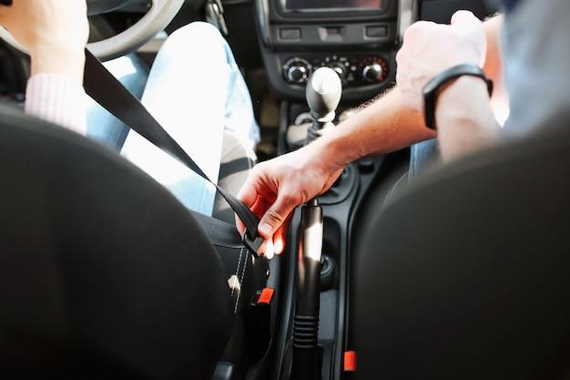 男性の自動インストラクターが若い女性で試験を受けます。男は女の子のシートベルトを手に持って、それをロックしたいと思っています。ビューを切り取ります。車に座っています。若い女性を調べます。