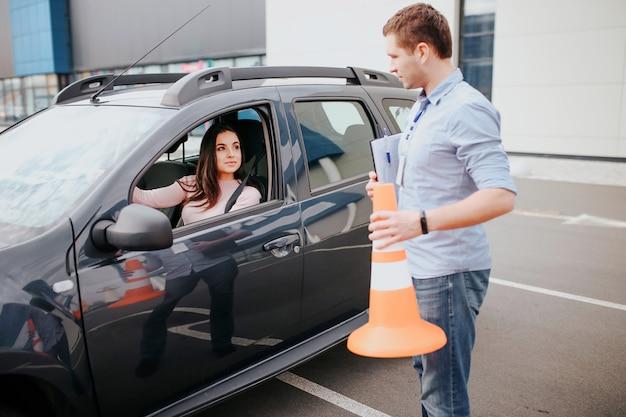 男性の自動インストラクターが若い女性で試験を受けます。オレンジ色のサインインの手で車の外に立ちます。車の中で女性を見てください。女子学生がステアリングホイールに手を添えてインストラクターを見てください。