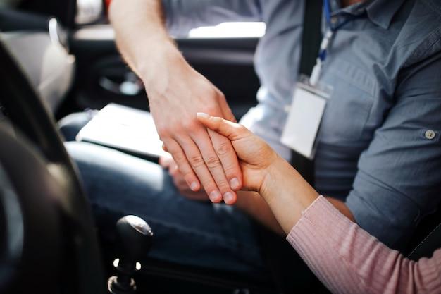 Мужской авто инструктор сдает экзамен у молодой женщины