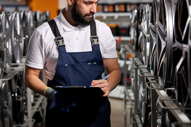 Male auto mechanic checking new tires and discs in auto shop, preparing for sale, automobiles industry, bearded male in uniform at work place making notes