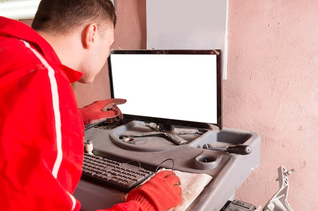 Male auto mechanic checking the readout on a computer hooked to a car elevated