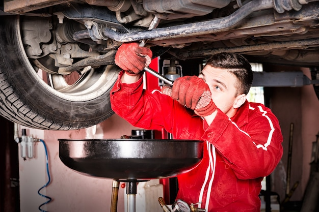 Male auto mechanic in uniform working underneath a lifted car