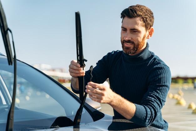 通りでフロントガラスのワイパーをチェックしている男性の自動車所有者。男は車のワイパーを交換しています。自動車修理コンセプト