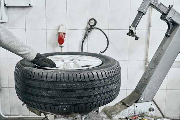 Male auto technician replacing old tire on wheel in garage