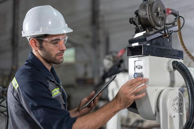 男性の自動化エンジニアが、産業工場でタブレットを使用してロボットアーム溶接機をチェックおよび検査制御します。人工知能の概念。