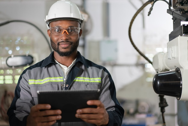 男性の自動化エンジニアは、産業工場で検査ロボットアーム溶接機のタブレットを保持します