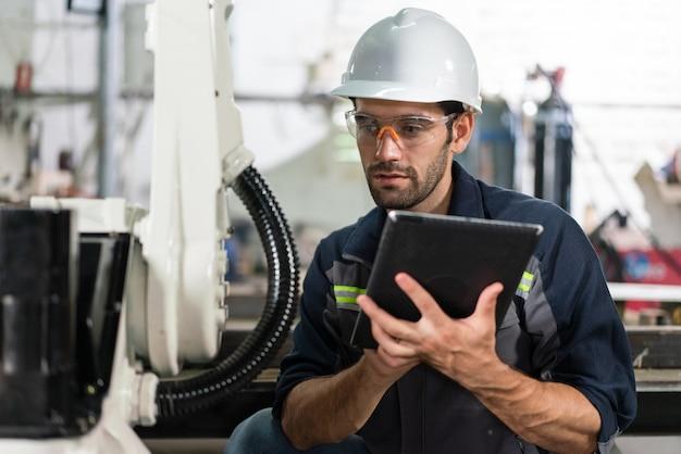 男性の自動化エンジニアの検査は、工場でタブレットを備えたロボットアーム溶接機を制御します
