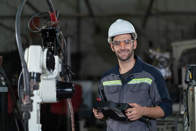 工場で制御ロボットアーム溶接機のリモートボードを笑顔で保持する男性の自動化エンジニア