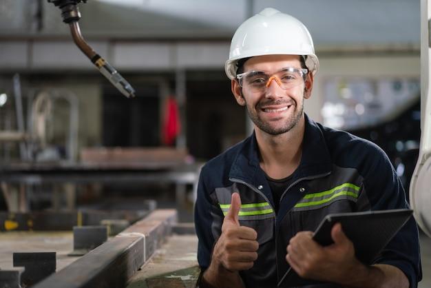 工場で検査ロボットアーム溶接機のホールドタブレットを笑顔の男性の自動化エンジニア