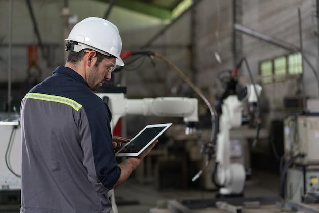 産業工場でタブレット制御ロボットアーム溶接機を使用する男性の自動化エンジニア人工知能