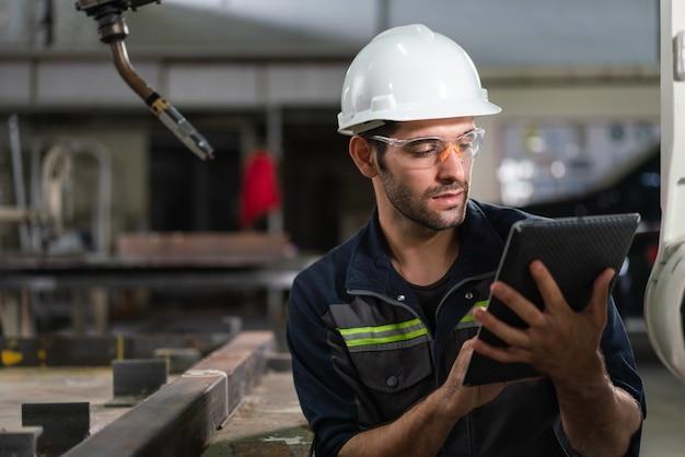 産業工場でタブレット制御ロボットアーム溶接機を使用する男性の自動化エンジニア