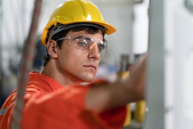 男性の自動化エンジニアは、オレンジ色の制服を着て、ヘルメットの安全検査を行い、産業工場のロボット アーム溶接機を制御します。人工知能のコンセプト。