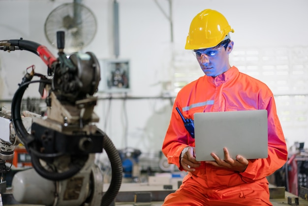 Male automation engineer wear an orange uniform with helmet safety coding a program in a laptop for control of a robot arm welding machine in an industrial factory. artificial intelligence concept.