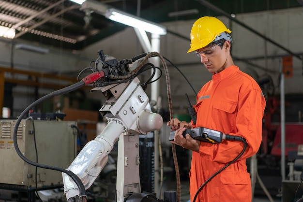 Male automation engineer wear an orange uniform with helmet safety standing control a robot arm welding machine with a remote system board in an industrial factory. artificial intelligence concept.