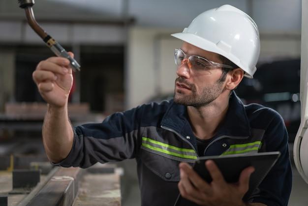 産業工場でタブレットのデータ仕様でロボット溶接ヘッドをチェックする男性の自動化エンジニアの溶接工。