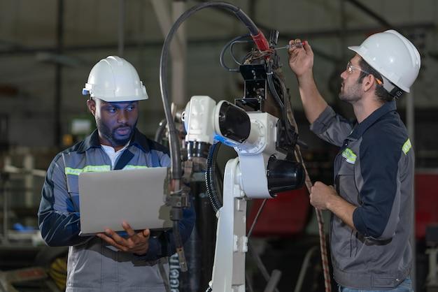 남성 자동화 엔지니어는 공장에서 노트북으로 로봇 팔 용접기를 수리하고 검사합니다.