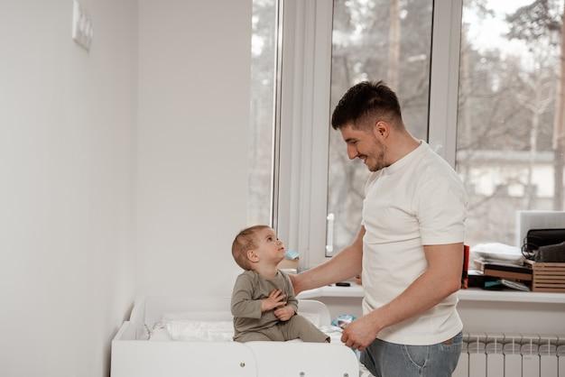 男性のベビーシッターは、日中の睡眠の準備をし、笑顔で子供に寝る時間だと説明します