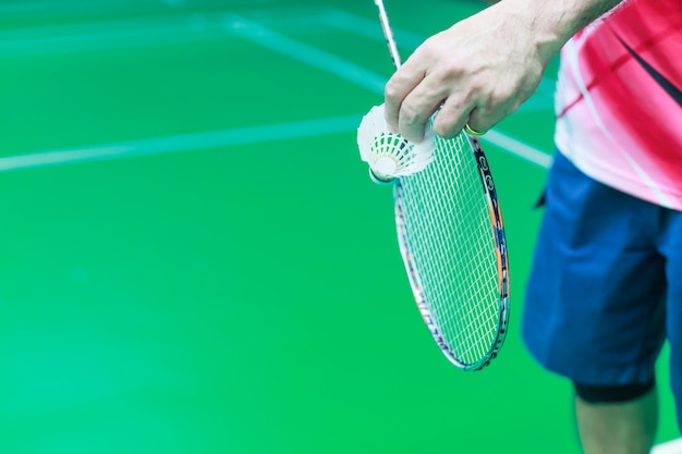 Male badminton single player hand holds white shuttle cock together with racket
