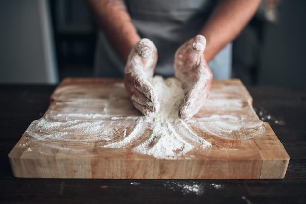 Мужские руки пекаря замешивают тесто на разделочной доске. приготовление хлеба. домашняя выпечка