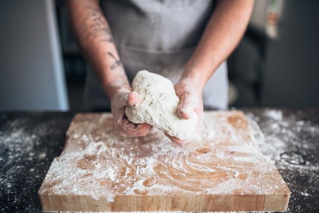 Мужские руки пекаря замешивают тесто на деревянном столе. приготовление хлеба. домашняя выпечка
