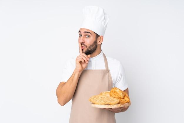 沈黙のジェスチャーをしている白で隔離のいくつかのパンとテーブルを保持している男性のパン屋